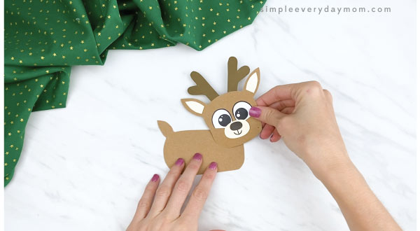 hands gluing reindeer head to finger puppet body