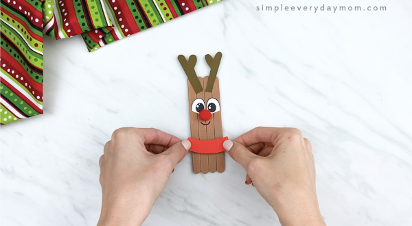 hands gluing collars on popsicle stick reindeer