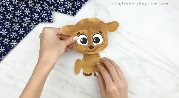 hands gluing reindeer head to body