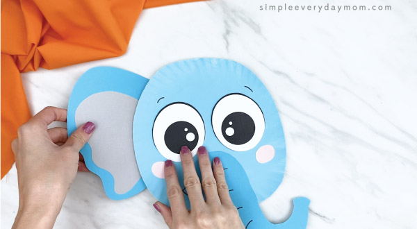 hands gluing ears onto paper plate elephant craft