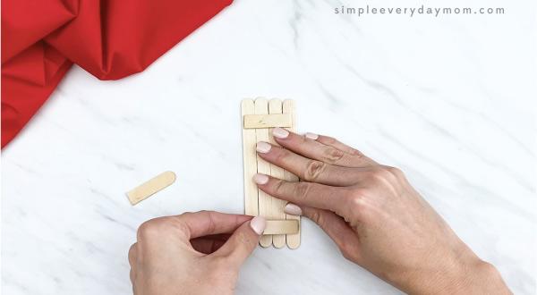 hands gluing popsicle stick together