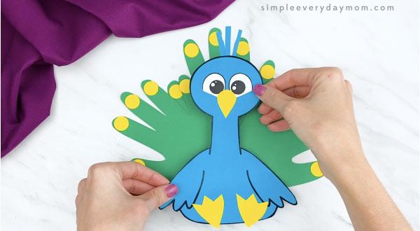 hands gluing body onto handprint peacock craft