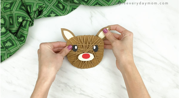hands gluing ears to yarn wrapped reindeer craft