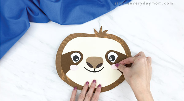 hands gluing cheeks to paper plate sloth craft