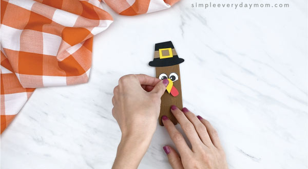 hands gluing beak onto popsicle stick turkey craft