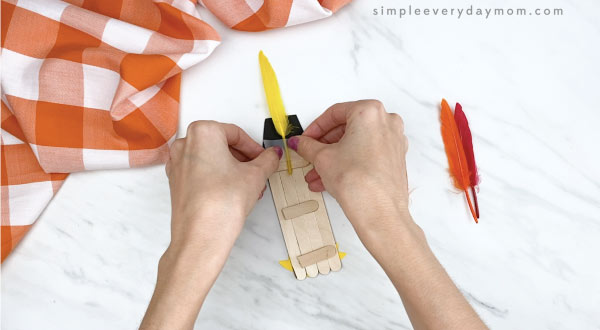 hands gluing feathers onto popsicle stick turkey craft