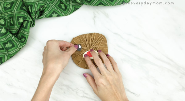 hands gluing eyes to yarn wrapped reindeer craft