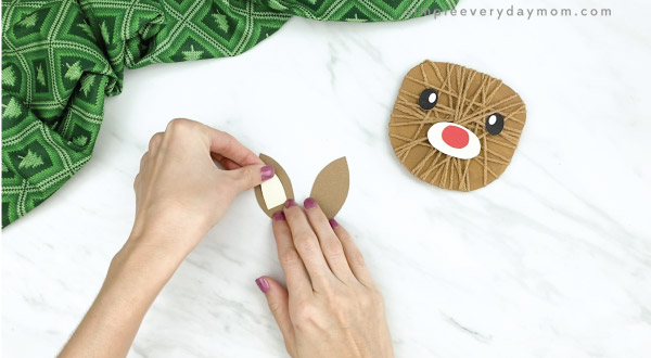 hands gluing inner ears to outer ears of reindeer craft