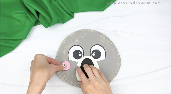 hand gluing cheek to paper plate koala