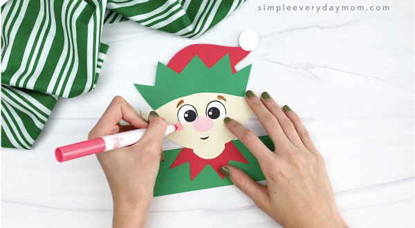 hands drawing cheek onto elf headband craft