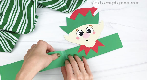 hands taping extender onto elf headband craft