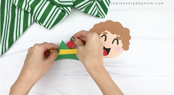 hands gluing feather to paper elf hat