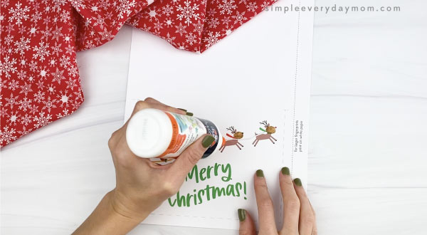 hands placing liquid glue line on christmas card
