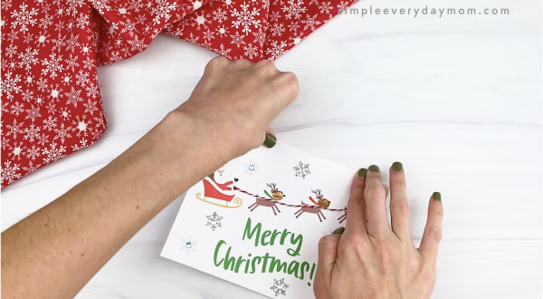 hands folding homemade christmas card in half