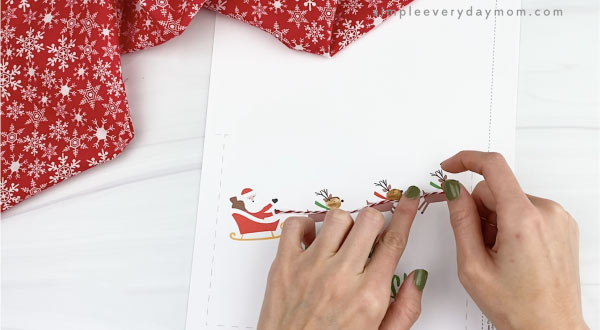 hand gluing red bakers twine to christmas card