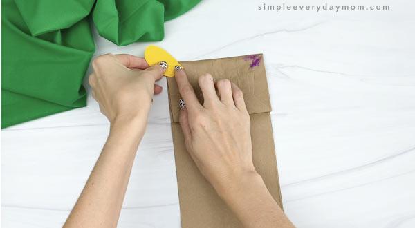 hands gluing ears to paper bag giraffe craft