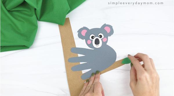 hands gluing leaves to handprint koala craft