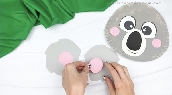 hand gluing inner ear to outer ear of paper plate koala craft