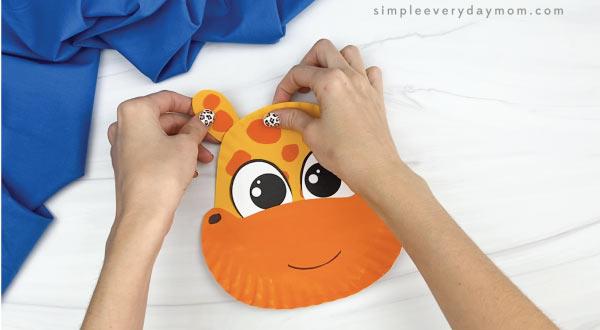 hands gluing ears to paper plate giraffe