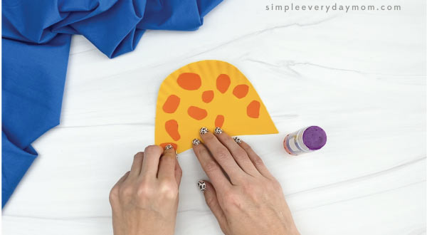 hands gluing spots to paper plate giraffe