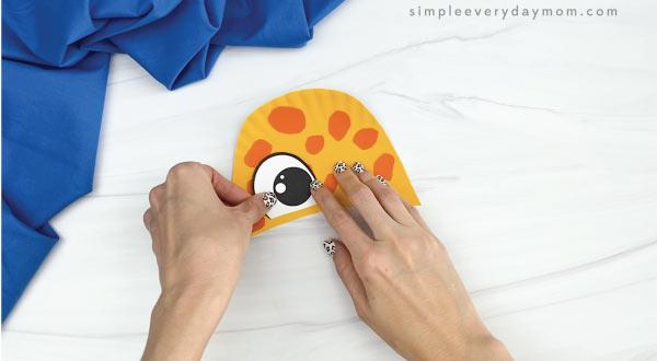 hands gluing eyes to paper plate giraffe