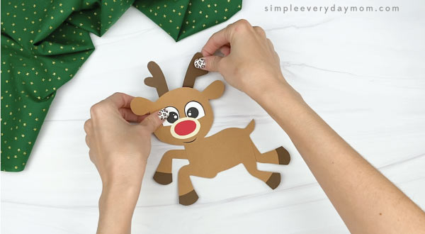 hands gluing antlers to paper rudolph craft