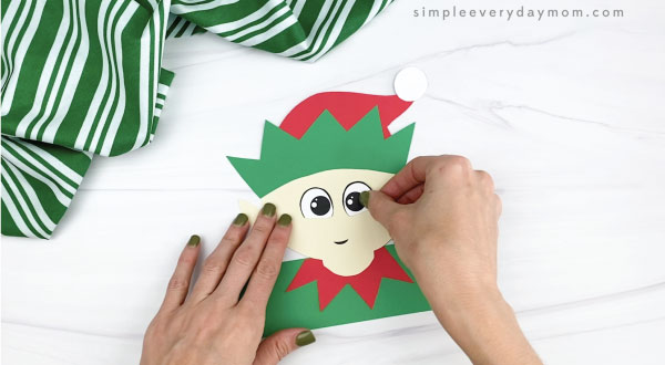 hands gluing eyes to elf headband craft