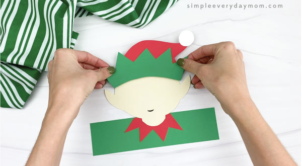 hands gluing hat to elf headband craft