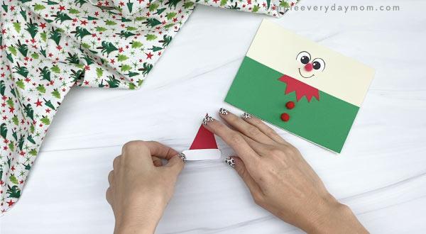 hands gluing elf hat together