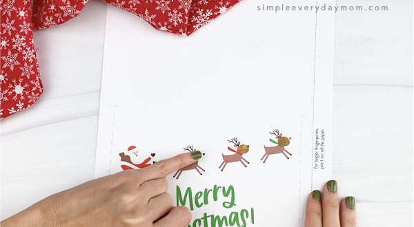 hands making paint fingerprint on reindeer card