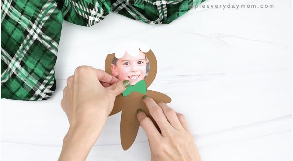 hand gluing bow photo to gingerbread man craft