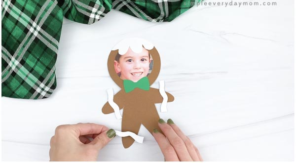 hand gluing icing decorations photo to gingerbread man craft