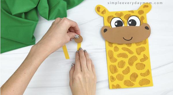 hands gluing paper bag giraffe horns together