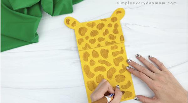 hands drawing spots on paper bag giraffe craft