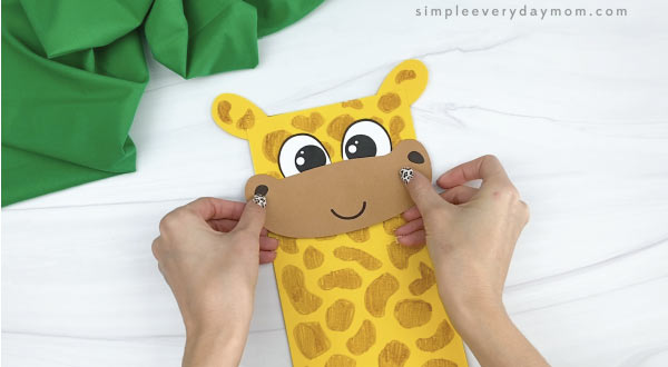 hands gluing mouth to paper bag giraffe craft