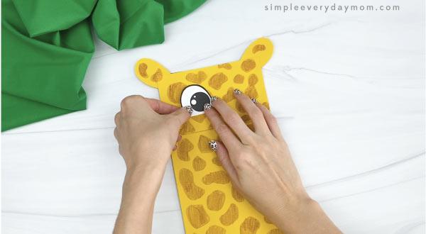 hands gluing eyes to paper bag giraffe craft