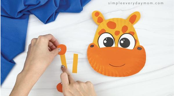 hands gluing paper plate giraffe horn together