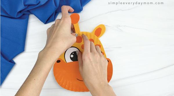 hands gluing horns to paper plate giraffe
