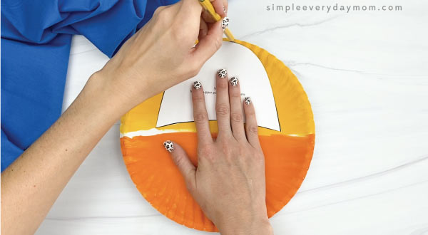 hands tracing giraffe head template onto painted paper plate