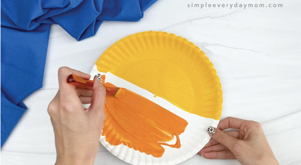 hands painting paper plate orange