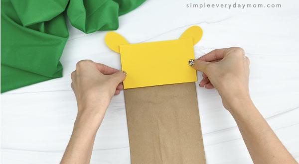 hands gluing head to paper bag giraffe craft