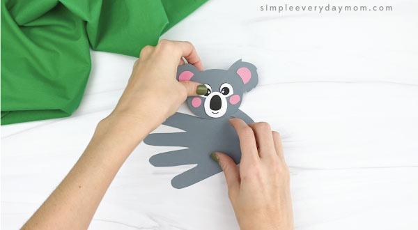 hands gluing head to handprint koala craft