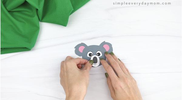 hands gluing nose to handprint koala craft