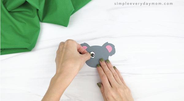 hands gluing eyes to handprint koala craft