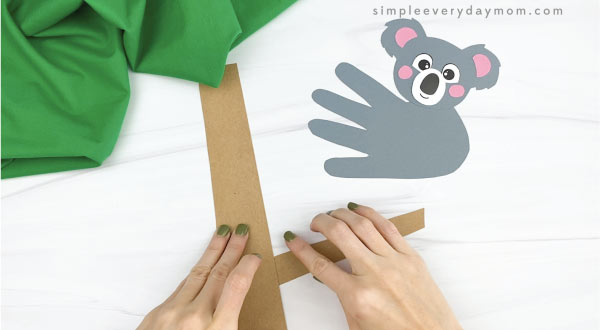 hands gluing paper tree branch to tree trunk