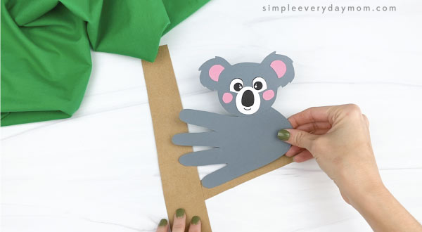 hand gluing handprint koala craft to paper tree