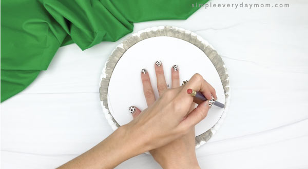 hand tracing template onto paper plate