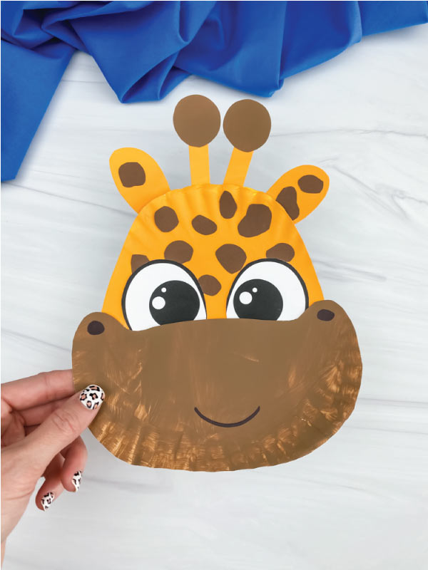 hand holding brown and yellow paper plate giraffe craft