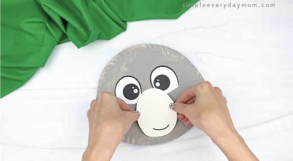 hand gluing mouth to paper plate koala