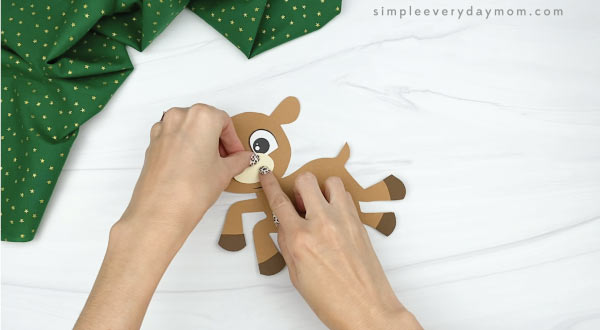 hands gluing muzzle to paper rudolph craft
